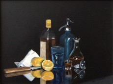 Still life with bottles and sliced lemon on glass table
