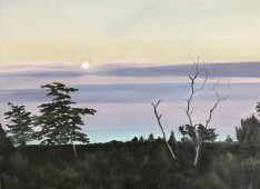 Moon rising behind clouded sunset sky