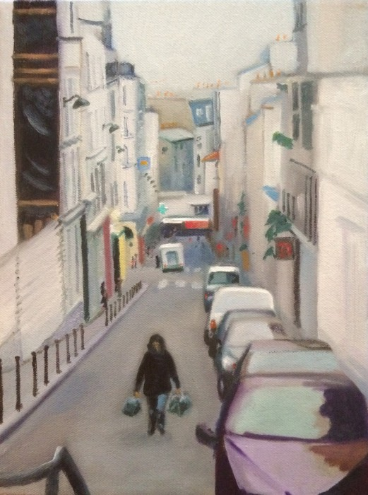 Montmartre street scene of woman walking uphill carrying bags
