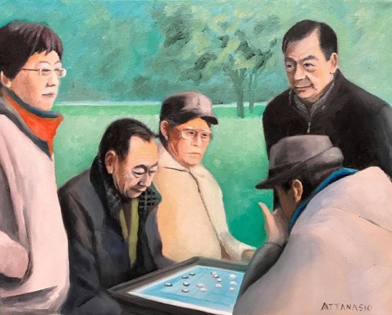 Men playing game in park, with bystanders